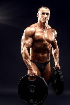 Retrato de fisiculturista com halteres nos braços