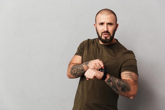 Retrato de fisiculturista masculino em camiseta casual posando usando smartwatch no pulso, isolado sobre a parede cinza