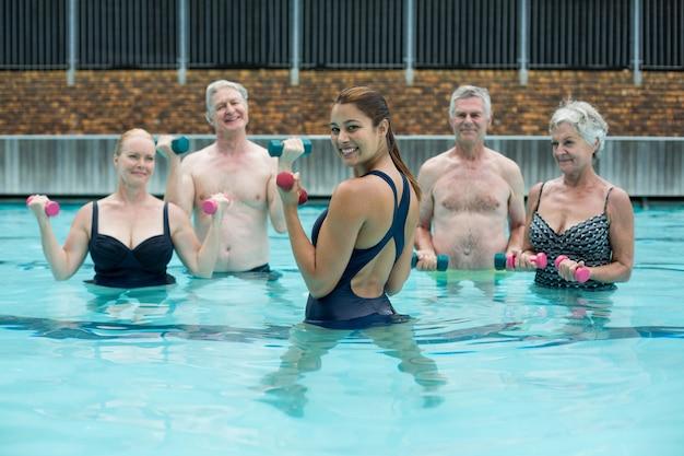 Retrato de forte treinadora feminina com nadadores sênior na piscina