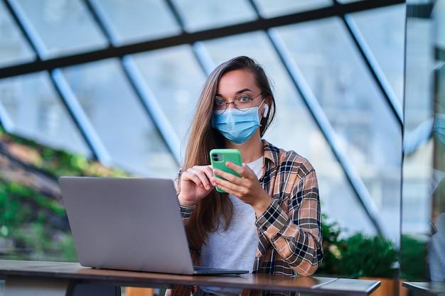 Retrato de freelancer de mulher em máscara protetora, fones de ouvido sem fio e óculos redondos usando telefone e computador para trabalho remoto on-line no café. proteção da saúde em locais públicos