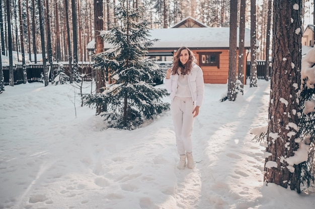 Retrato de frio ensolarado de inverno na neve de uma mulher jovem e bonita em uma jaqueta branca e quente no quintal de uma casa de madeira