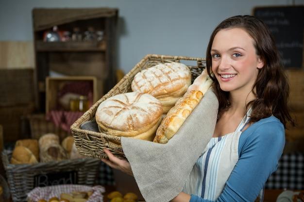 Retrato de funcionária segurando uma cesta de pão