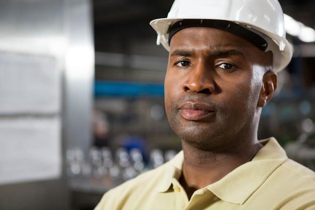 Retrato de funcionário sério do sexo masculino usando capacete na fábrica
