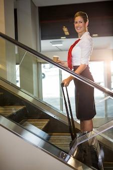Retrato de funcionários do sexo feminino com bagagem na escada rolante
