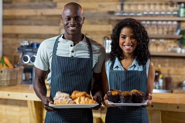 Retrato de garçom e garçonete segurando um prato de bolinho e croissant