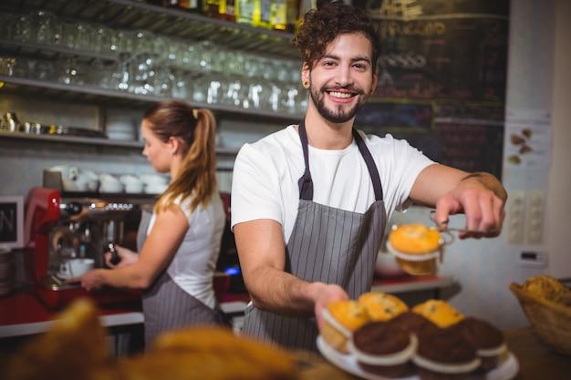 Retrato de garçom segurando um prato de bolo do copo no balcão