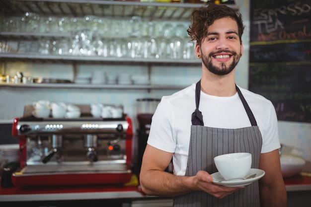 Retrato de garçom segurando xícara de café