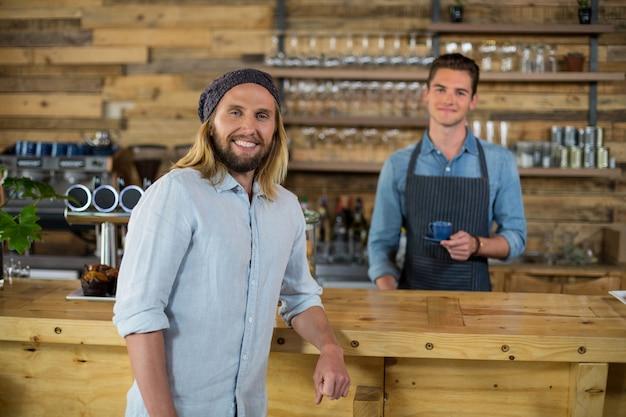 Retrato de garçom servindo café para homem no balcão