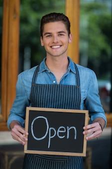 Retrato de garçom sorridente mostrando lousa com sinal aberto