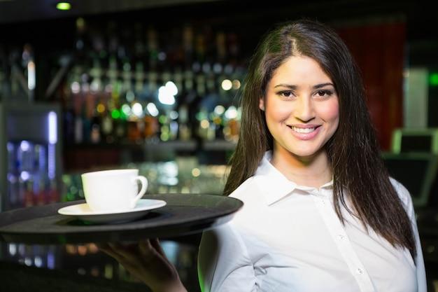 Retrato de garçonete bonita servindo uma xícara de café em bar