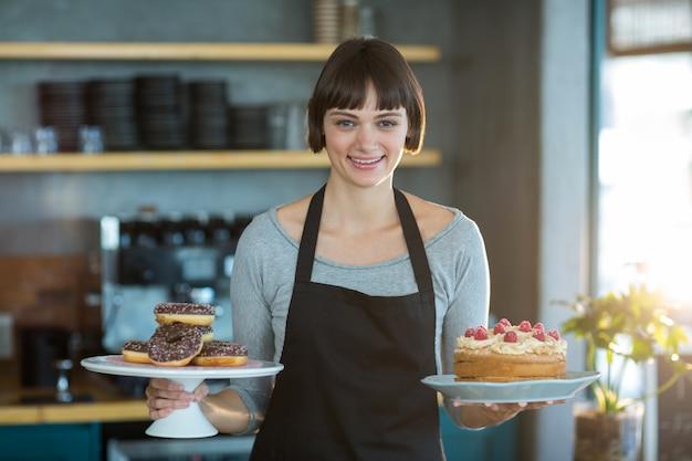 Retrato de garçonete segurando rosquinhas e bolo no café