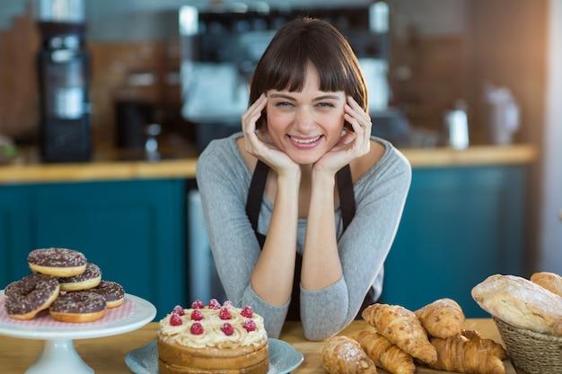 Retrato de garçonete sentado no balcão com alimentos doces na mesa