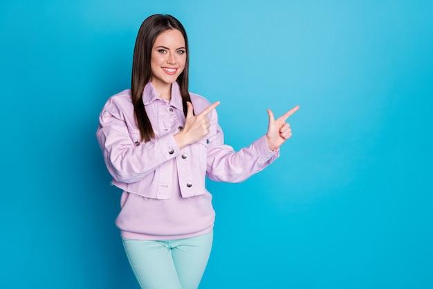 Retrato de garota promotora apontar dedo copyspace isolado fundo de cor azul