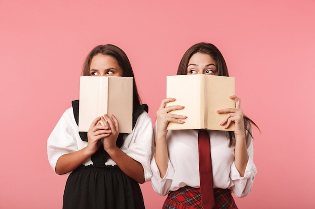 Retrato de garotas engraçadas em uniforme escolar lendo livros, em pé, isolado na parede vermelha