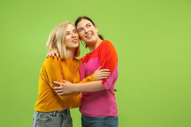 Retrato de garotas muito charmosas em roupas casuais isoladas na parede verde do estúdio