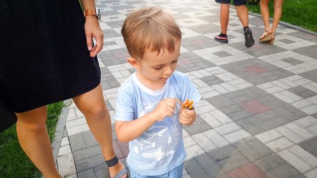 Retrato de garotinho concentrado brincando com o helicóptero de brinquedo no parque