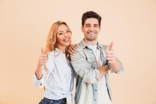 Retrato de gente bonita, homem e mulher em roupas básicas, posando com o polegar para cima, isolado sobre uma parede bege