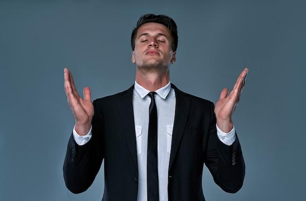 Retrato de gerente atraente orando com as mãos ao alto, isoladas em cinza. conceito de esperança e crença.