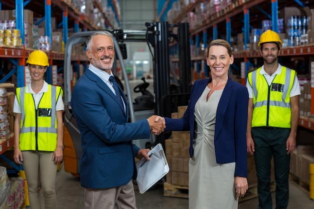 Retrato de gerente de armazém, apertando as mãos com o cliente