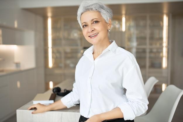 Retrato de gerente de evento feminino de meia-idade com corte de cabelo elegante trabalhando em seu escritório