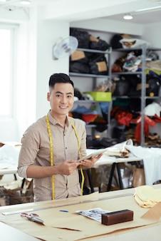 Retrato de gerente de oficina de costura sorridente com computador tablet em pé na mesa grande e sorrindo um.