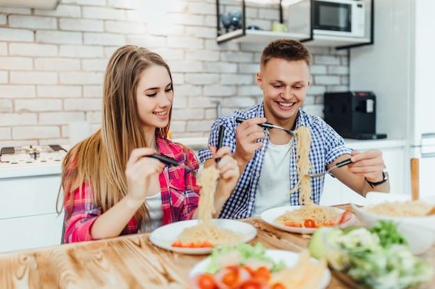 Retrato de giro feliz em cheeful ação degustação e cheirando o café da manhã da mesa de macarrão decorada com ingredientes da comida na cozinha moderna e se divertindo.