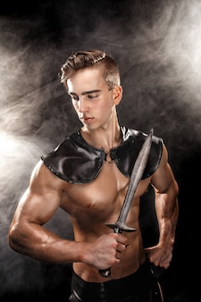 Retrato de gladiador muscular bonito com espada. isolado. fotografia de estúdio