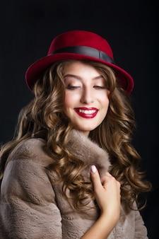 Retrato de glamour do modelo de mulher bonita com lábios vermelhos e cabelos longos morena com casaco de pele de luxo e chapéu cor marsala