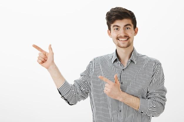 Retrato de glamour engraçado modelo masculino europeu com bigode e barba em camisa listrada, apontando para a esquerda com gestos de arma de dedo e sorrindo amplamente, invocando uma linda mulher para continuar falando no bar