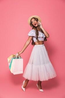 Retrato de glamour mulher bonita usando chapéu de palha e saia fofa segurando sacolas de papel colorido e falando no celular