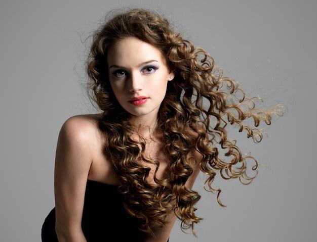Retrato de glamour, mulher jovem e bonita com cabelo longo cacheado
