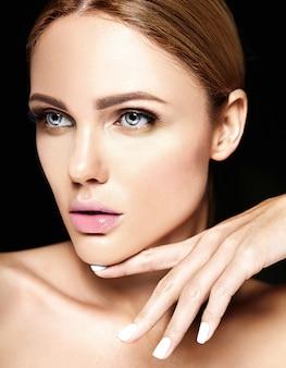 Retrato de glamour sensual do modelo de mulher bonita sem maquiagem e pele limpa e saudável em fundo preto