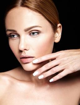 Retrato de glamour sensual do modelo de mulher bonita sem maquiagem e pele limpa e saudável em preto