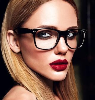 Retrato de glamour sensual do modelo de mulher loira bonita com maquiagem diária fresca com cor de lábios vermelhos e pele limpa e saudável em copos