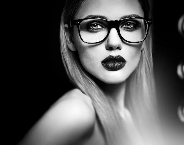 Retrato de glamour sensual do modelo de mulher loira bonita com maquiagem diária fresca com lábios roxos cor e pele limpa e saudável em copos. preto e branco