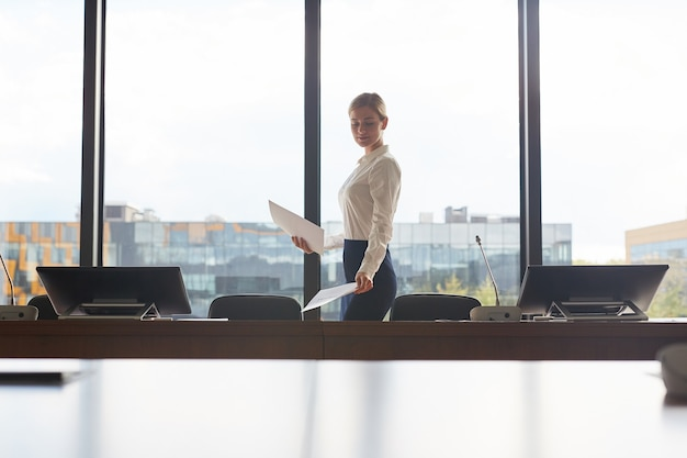 Retrato de grande angular da elegante secretária, exibindo documentos na mesa enquanto prepara a sala de conferências para o evento.