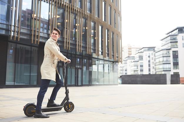 Retrato de grande angular de alegre jovem empresário vestindo sobretudo, olhando para trás enquanto andava de scooter elétrico com edifícios urbanos no fundo, copie o espaço