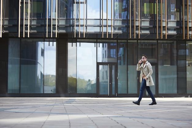 Retrato de grande angular de um empresário elegante vestindo sobretudo, atravessando a cena enquanto fala por smartphone, edifício urbano de vidro no fundo