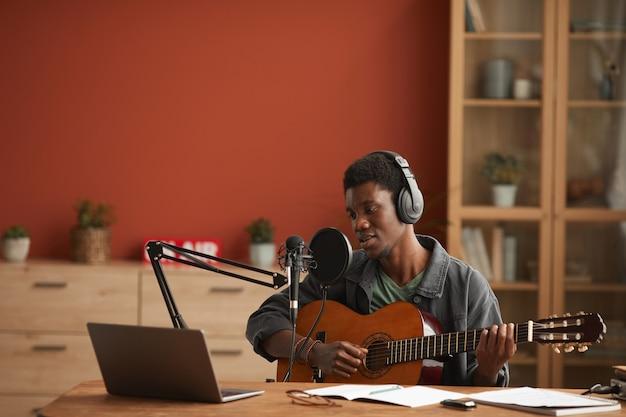 Retrato de grande angular de um homem afro-americano talentoso cantando ao microfone e tocando violão enquanto grava música no estúdio, copie o espaço
