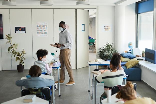 Retrato de grande angular de um professor afro-americano usando máscara na sala de aula da escola, medidas de segurança ambiciosas, copie o espaço