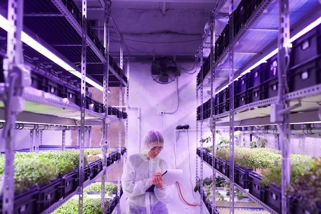 Retrato de grande angular de uma engenheira agrícola escrevendo na área de transferência enquanto está entre as prateleiras da estufa do viveiro de plantas iluminada por uma luz azul, copie o espaço