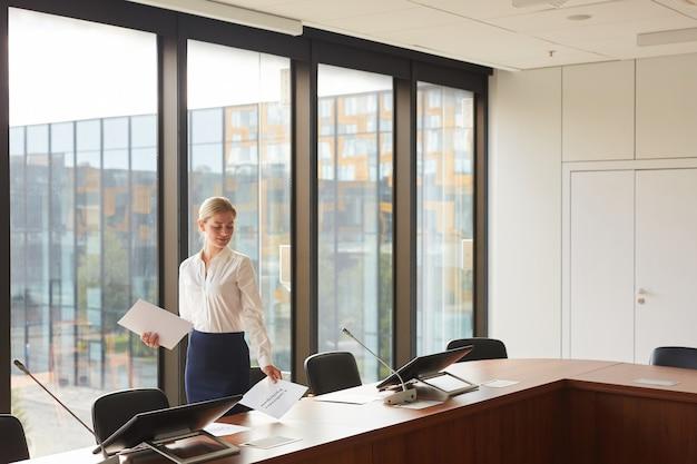 Retrato de grande angular de uma secretária loira exibindo documentos na mesa enquanto prepara a sala de conferências para o evento.
