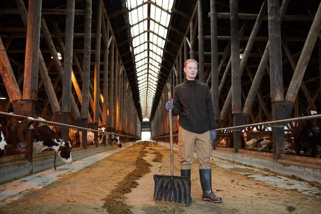 Retrato de grande angular de uma trabalhadora agrícola olhando para a câmera e segurando uma pá enquanto limpa o galpão de vacas no rancho da família, copie o espaço