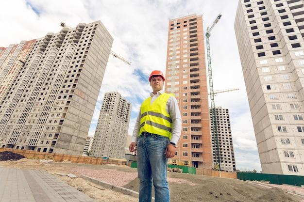 Retrato de grande angular do jovem encarregado da construção em pé no canteiro de obras
