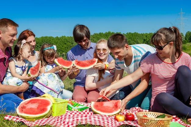 Retrato de grupo ao ar livre da empresa feliz fazendo piquenique na grama verde no parque e desfrutando de melancia