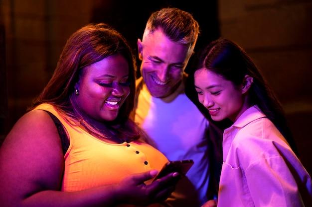 Retrato de grupo de amigos usando smartphone à noite nas luzes da cidade