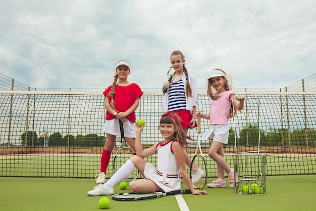 Retrato de grupo de garotas como tenistas segurando a raquete de tênis contra a grama verde da quadra ao ar livre