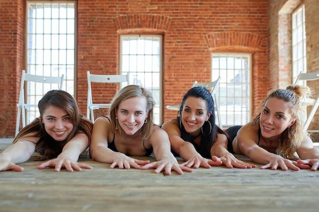 Retrato de grupo de jovens garotas bonitas e animadas com esteiras de ginástica em pé ao lado de uma parede branca, rindo e conversando. alunos engraçados à espera do início da aula