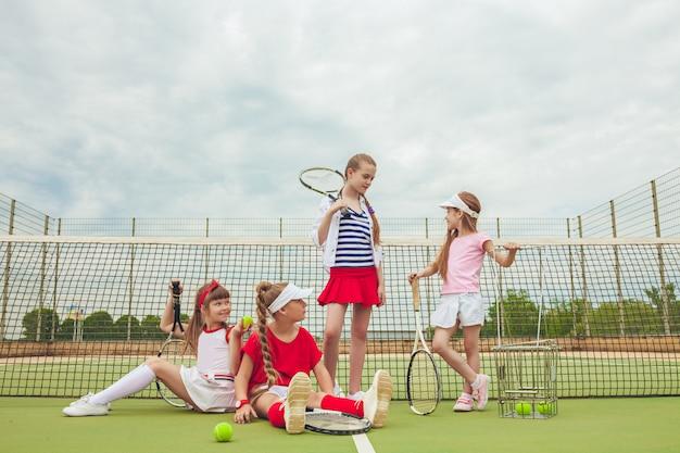 Retrato de grupo de meninas como tenistas segurando a raquete de tênis