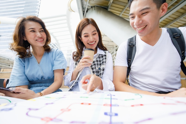 Retrato de grupo de três fofos jovens viajantes asiáticos sorridentes, sentado na escada, segurando um mapa do metrô em papel com uma mulher apontando na direção de uma estação com fundo desfocado de edifício alto.